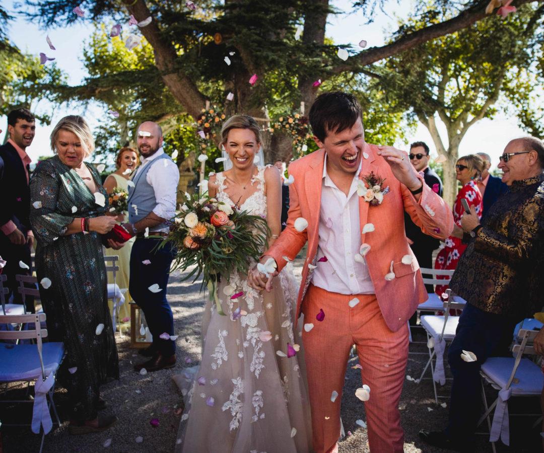 Sortie de cérémonie des mariés, les invités leurs jettent des prétals de fleurs