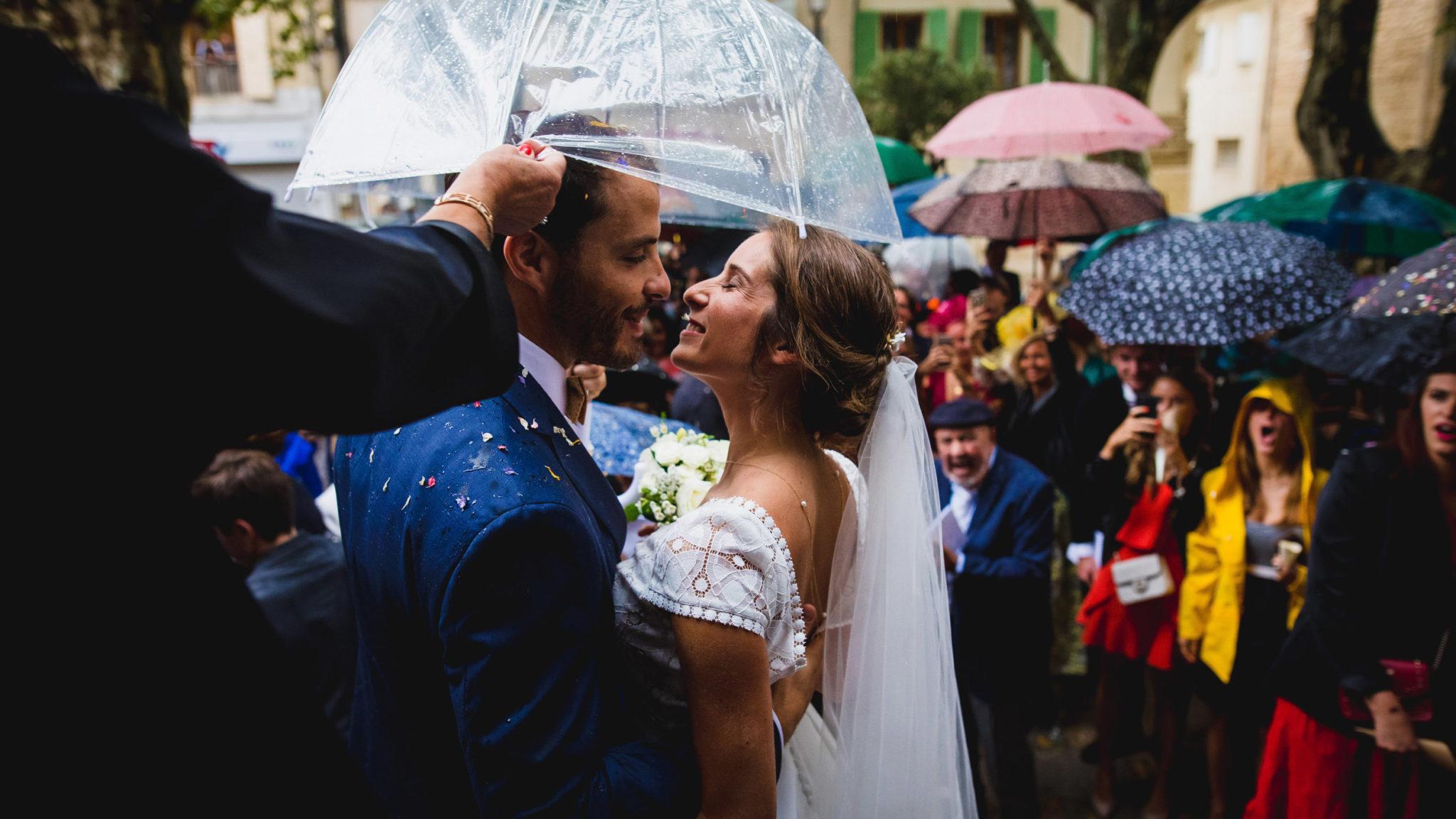 Bisous des mariés lors d'une sortie d'église sous la pluie