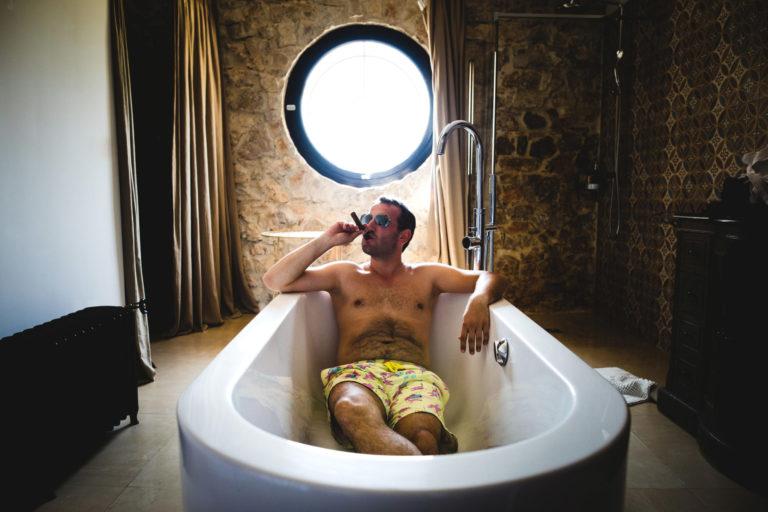 Le marié fume un cigare dans la baignoire