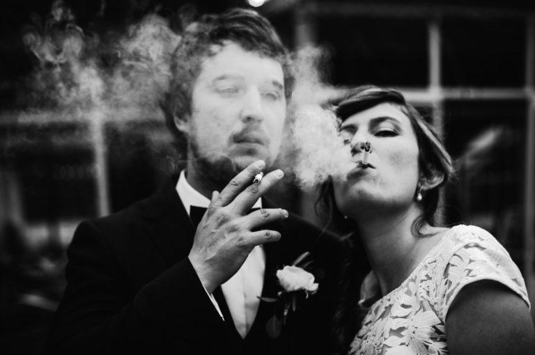 La mariée et le marié fument des cigarettes, photo en noir & blanc