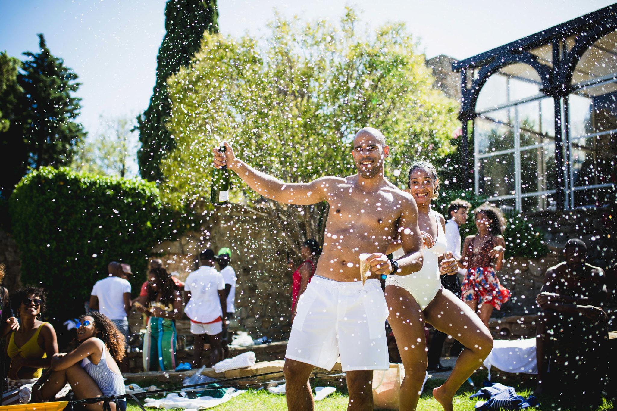 Les mariés en maillot de bain font gicler une bouteille de champagne pendant leur brunch
