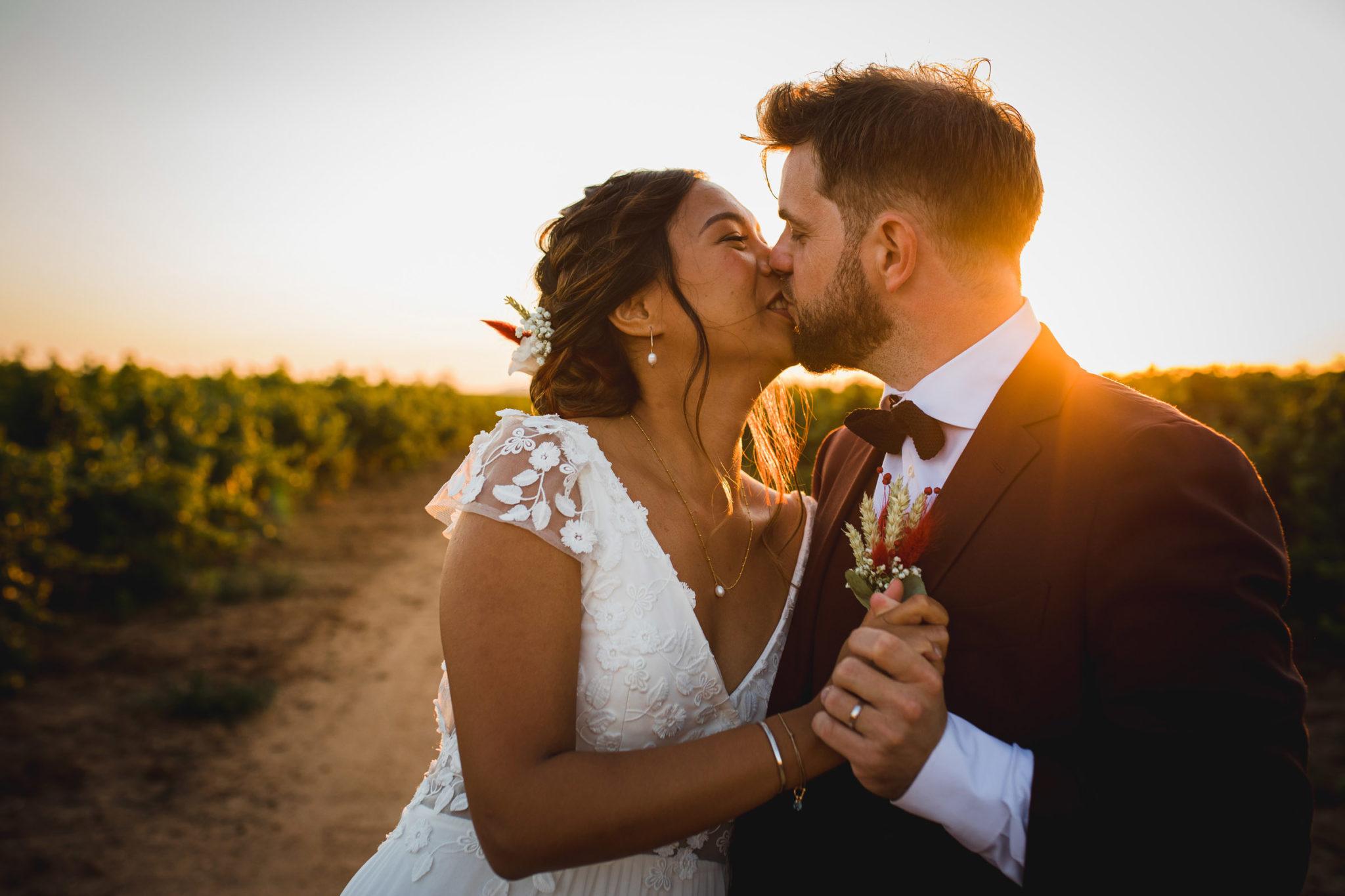 Les mariés s'embrassent devant un coucher de soleil