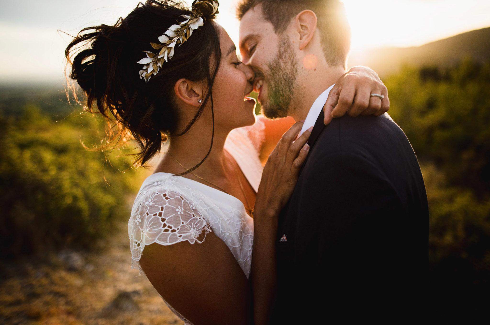 Une demie-seconde avant le bisou d'un couple de mariés devant un coucher de soleil