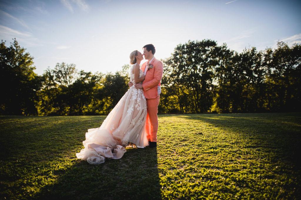 Duo de photographe et vidéaste : Photo de couple des mariés au grand angle sur la pelouse du domaine Provençal