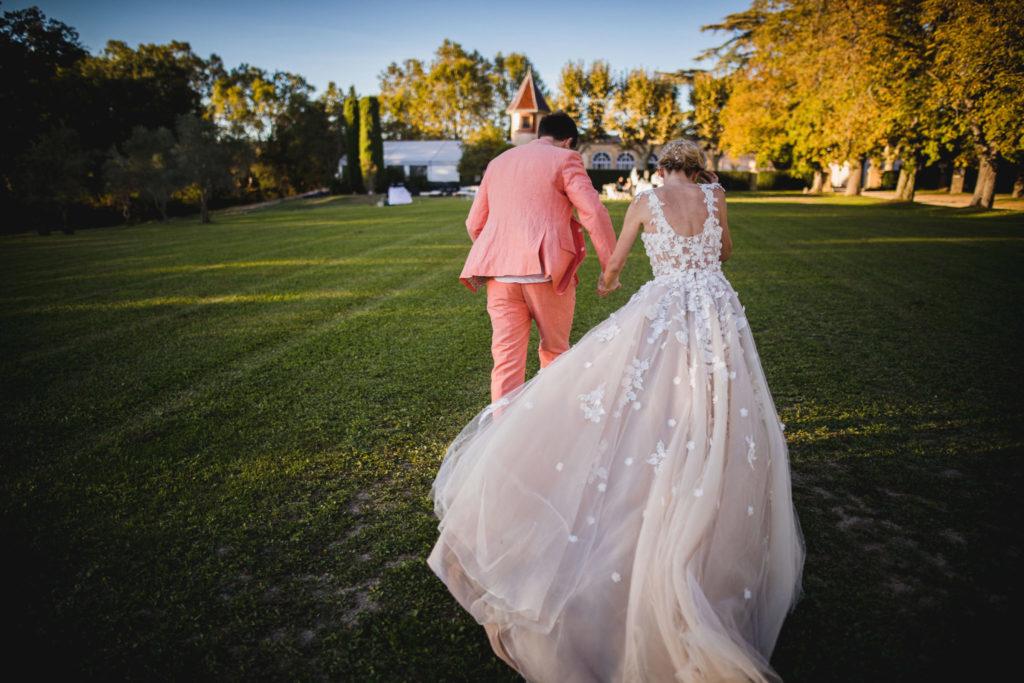 Les mariés se dirigent vers le repas de leur mariage de dos