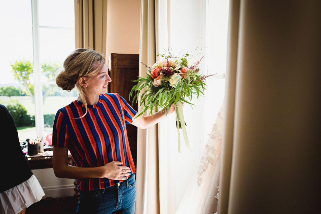 Duo de photographe et vidéaste : La future mariée observe son bouquet.