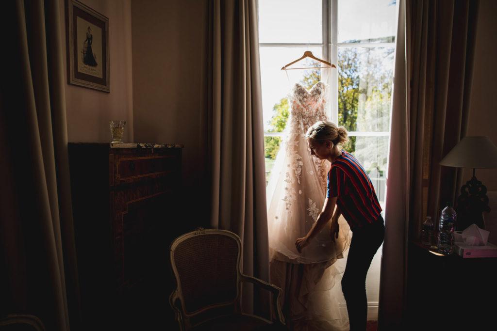 Duo de photographe et vidéaste : La future mariée met sa robe en place devant une fenêtre