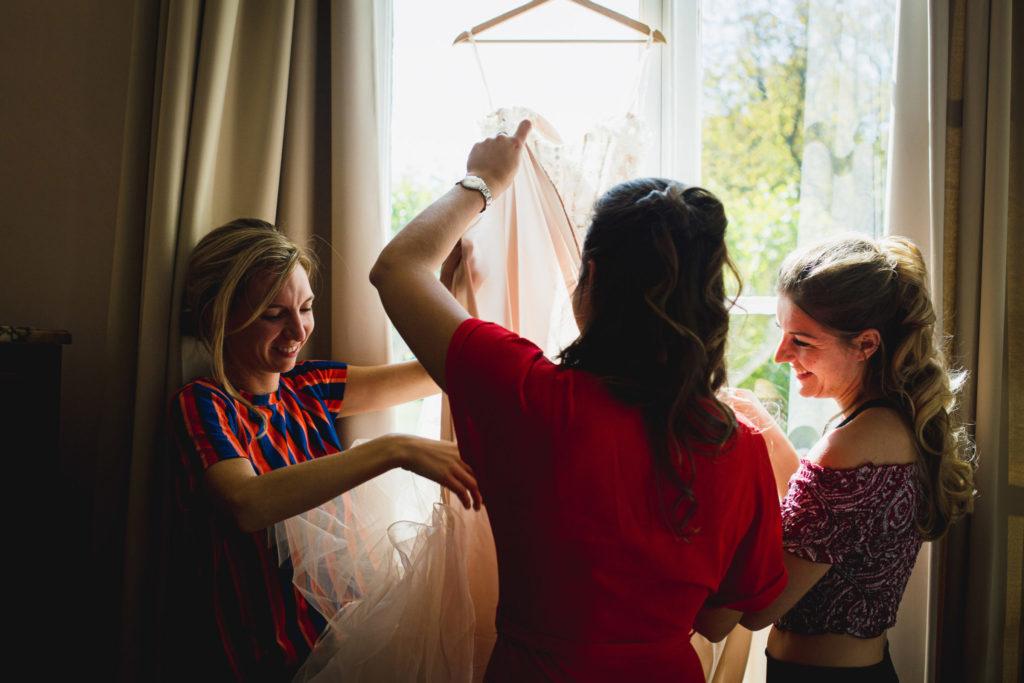 Duo de photographe et vidéaste : La future mariée et ses témoins rangent la robe devant une fenêtre