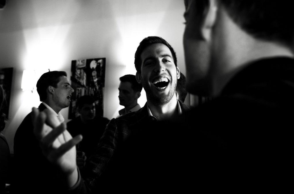 Photo de mariage : Homme avec un large sourire accueillant un ami