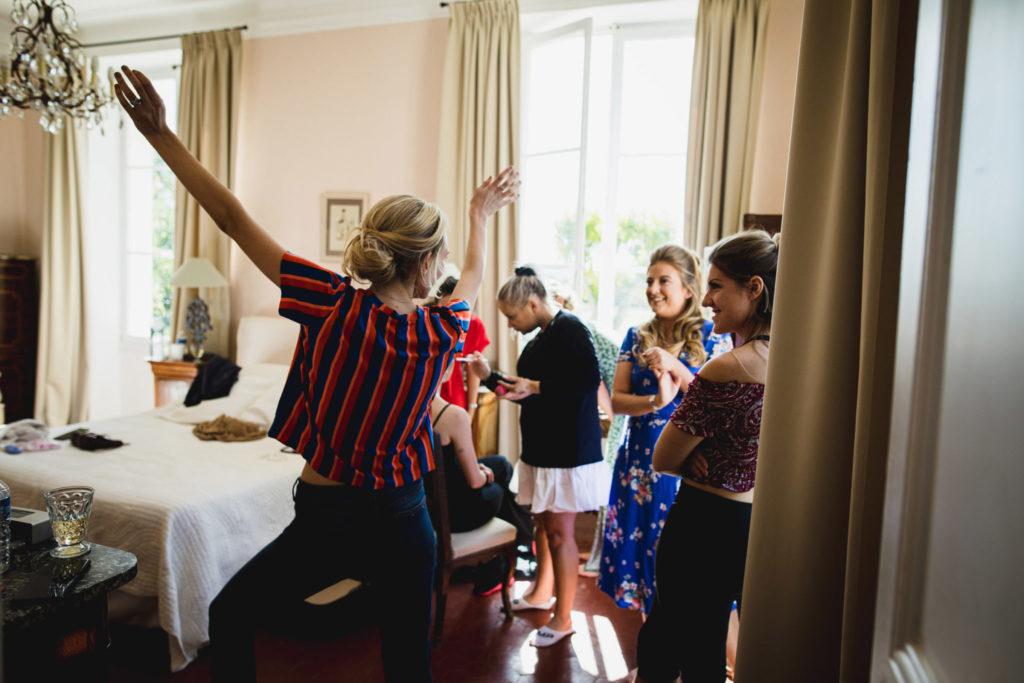 Duo de photographe et vidéaste : La future mariée danse de joie avec ses temoins pendant les préparatifs du mariage