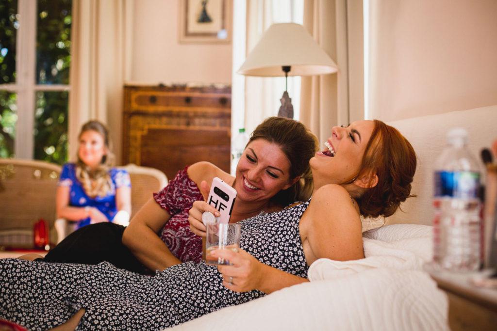 Photographe de mariage moderne qui rit devant son téléphone