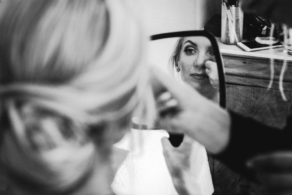 Photo de mariage : La mariée s'observe dans un miroir pendant son maquillage