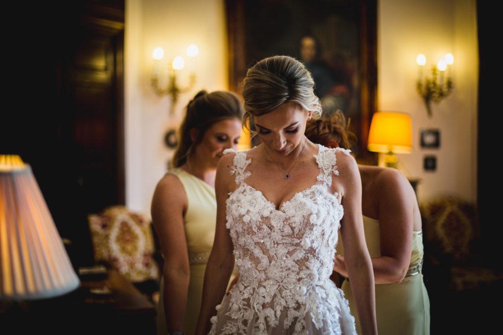 Duo de photographe et vidéaste : Les témoins ajustent la robe de la mariée
