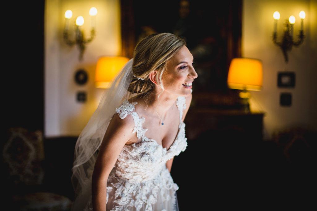 Duo de photographe et vidéaste : La mariée avec un grand sourire observe ses invités arriver à travers une fenêtre