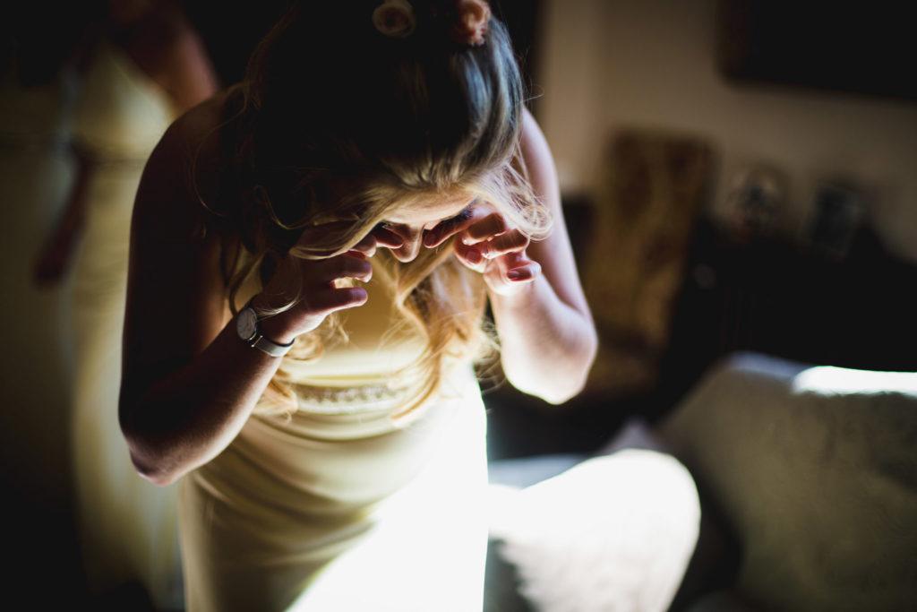 Duo de photographe et vidéaste : Une témoin de la mariée pleure pendant l'habillage