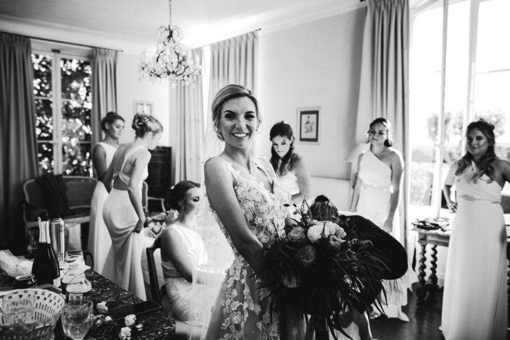 Duo de photographe et vidéaste : La mariée sourit en tenant son bouquet devant ses amies