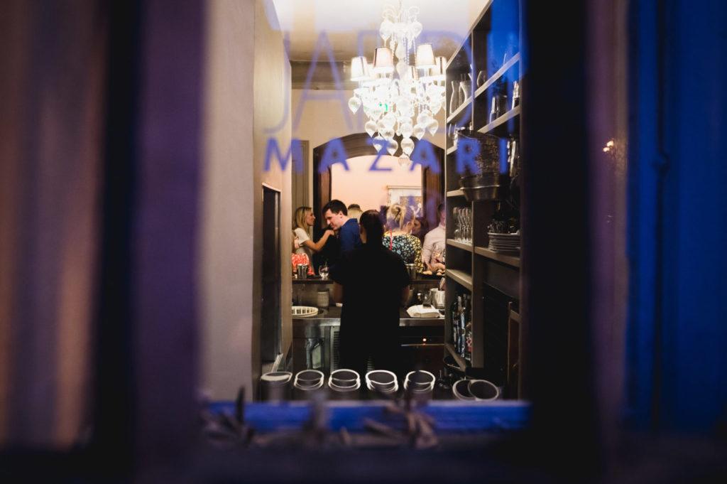 Photo de mariage : Vue des invités du mariage à travers une fenêtre du restaurant