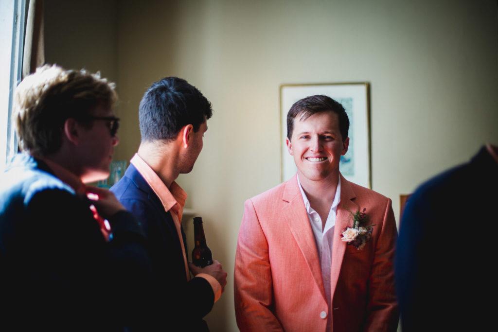 Le marié sourit à la photographe dans son magnifique costume couleur saumon