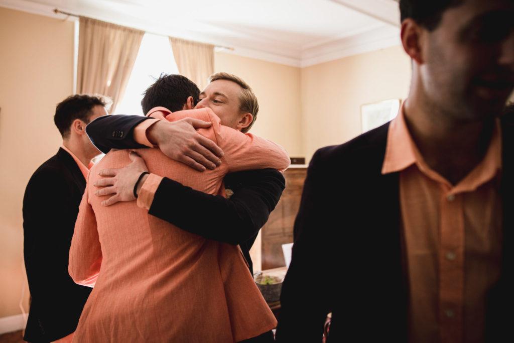 Le témoin prend le futur marié dans ses bras alors que les garçons sortent de la pièce pour rejoindre la cérémonie