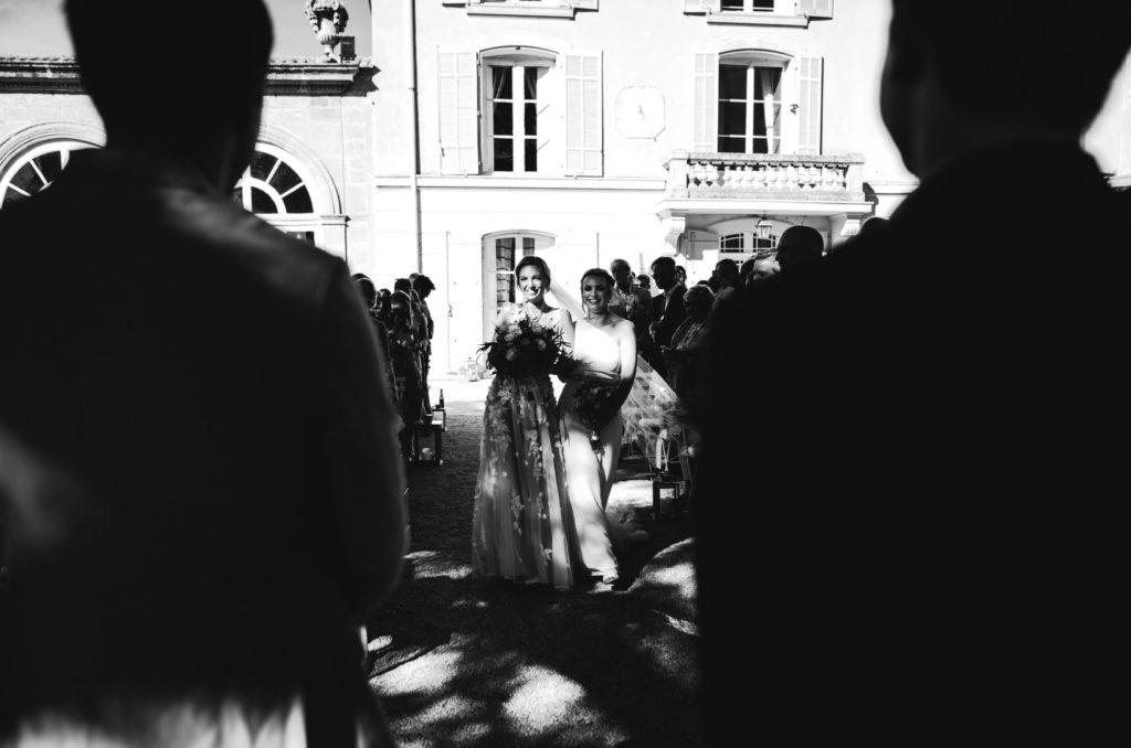 L'arrivée de la mariée au bras de sa témoin, en noir en blanc