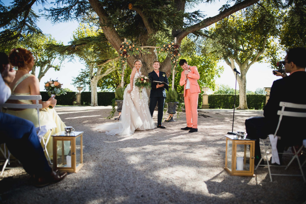 Les mariés devant l'arche de fleur de leur cérémonie laïque avec l'officiant