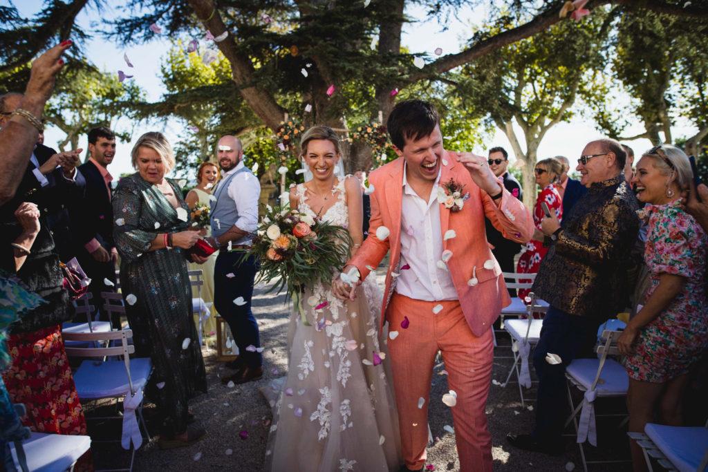 Lancé de pétales de rose sur les mariés lors de leur sortie de la cérémonie, le marié rit aux éclats