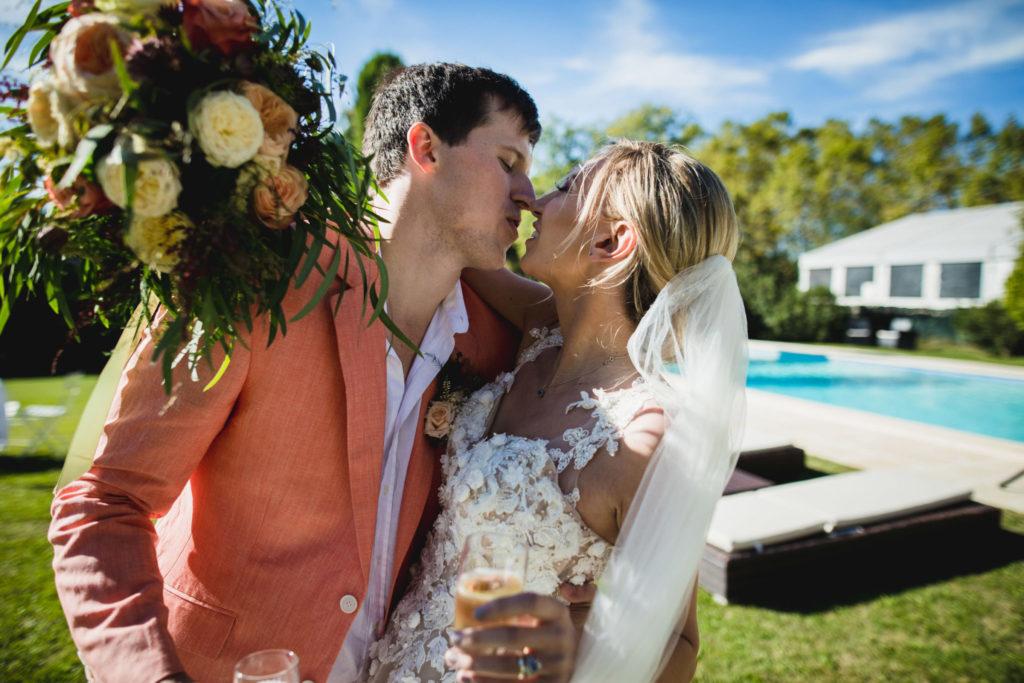 Duo de photographe et vidéaste : Le couple de mariés s'embrassent devant la piscine du domaine