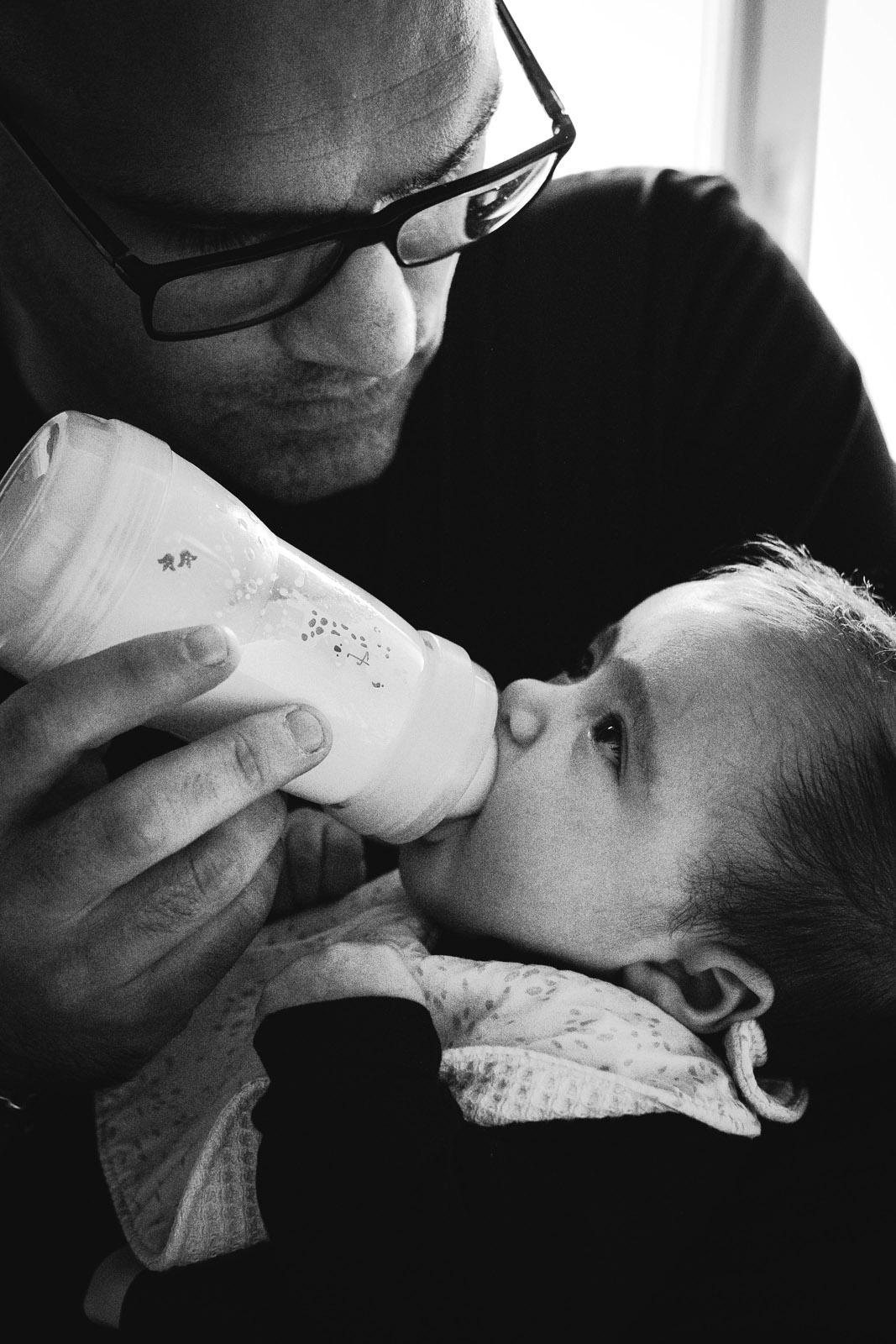 Un papa donne le biberon à son bébé, photo en noir & blanc