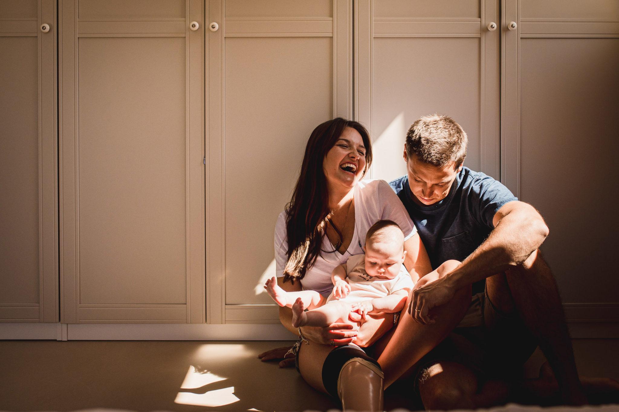 Jeune couple de parents avec leur bébé dans les bras, assis par terre dans la lumière d'une fenêtre