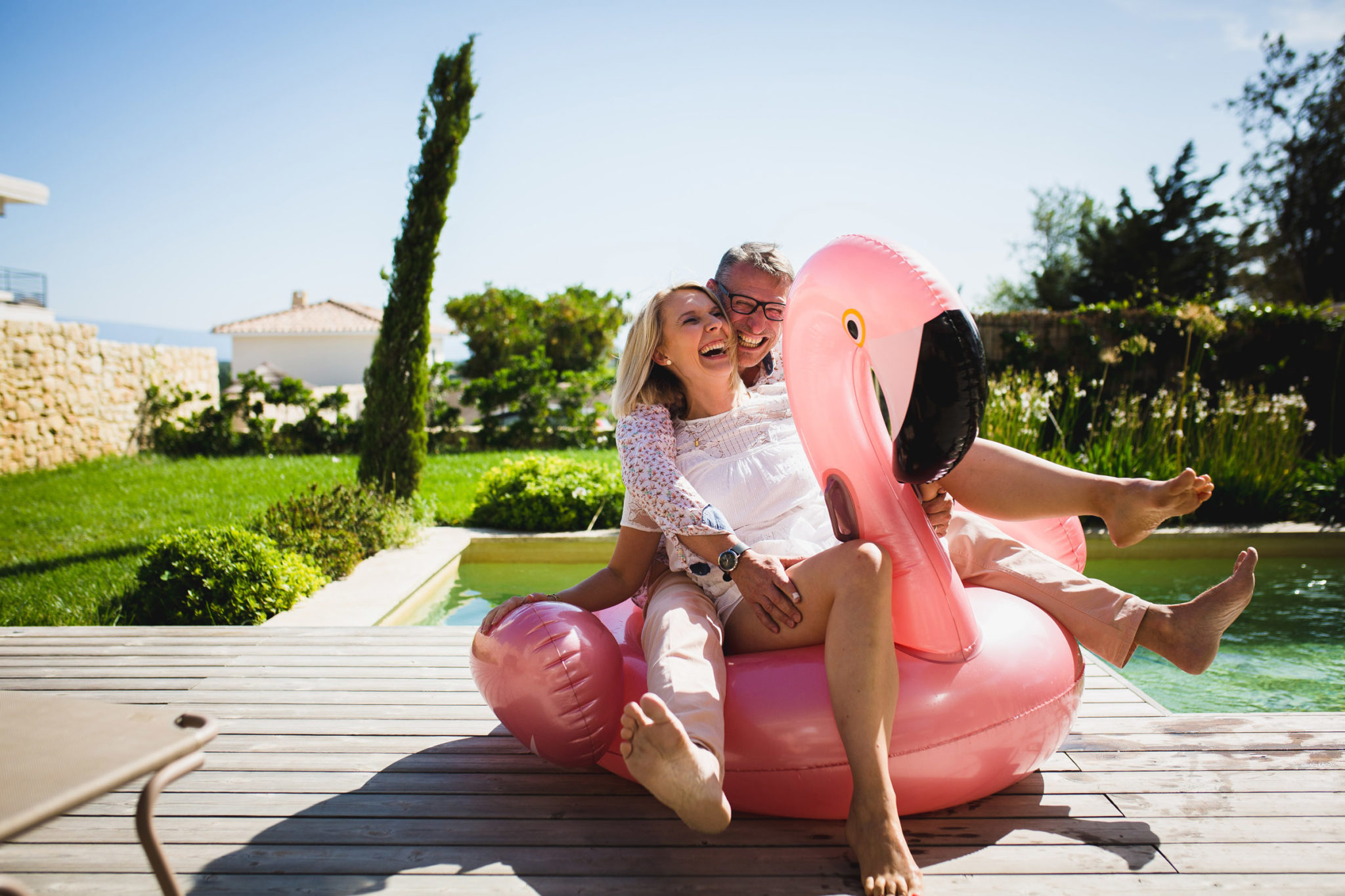 Couple assis sur une bouée flamand-rose au bord d'une piscine dans le Luberon
