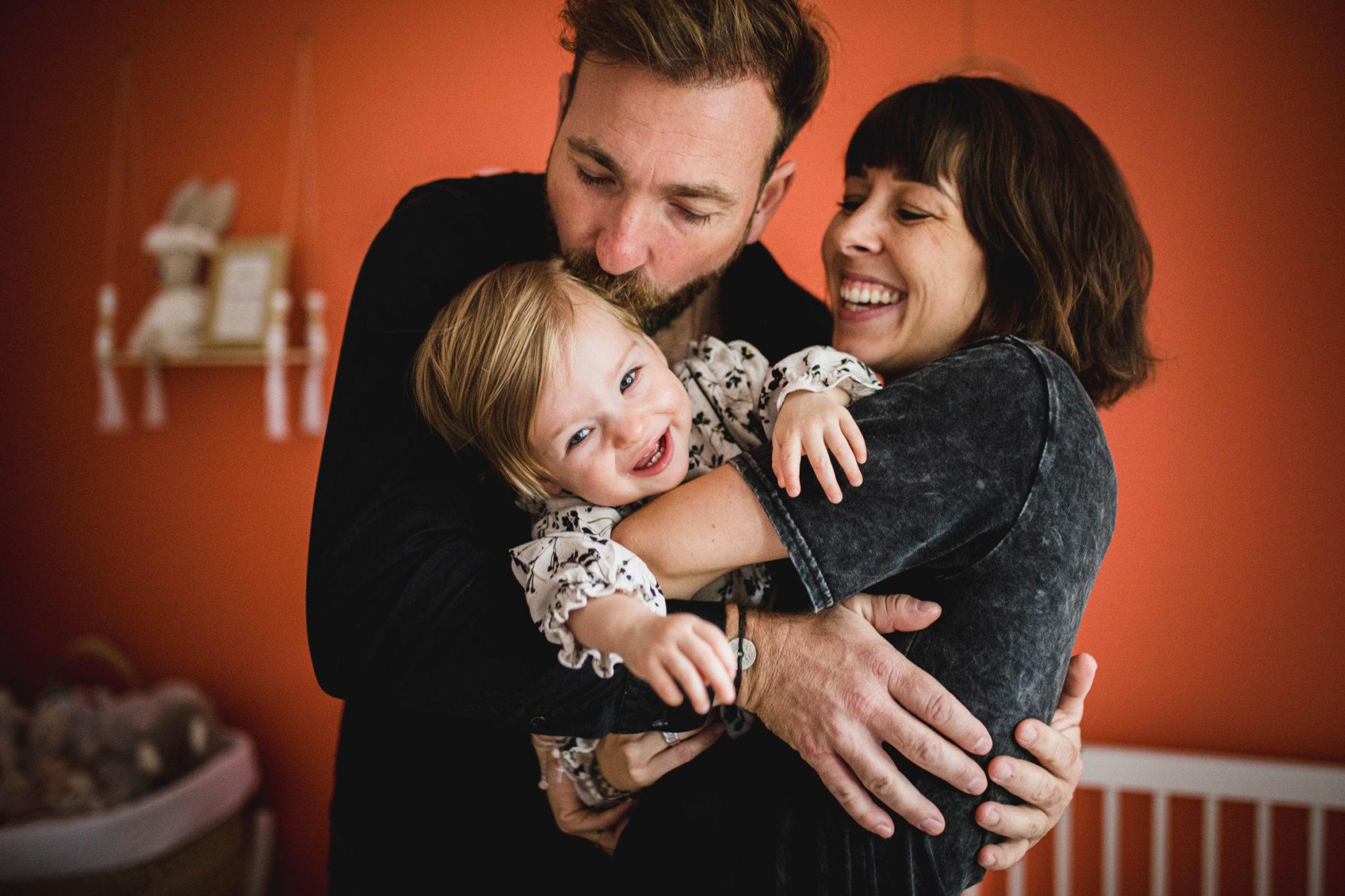 Un jeune couple de parents tiennent leur fille d'un an dans leurs bras dans une chambre orange d'une maison à Avignon