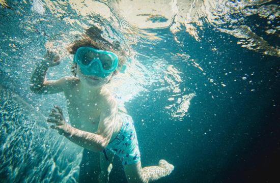 Jeune enfant de 3 ans porte un masque de plongée dans la piscine de sa maison à Avignon
