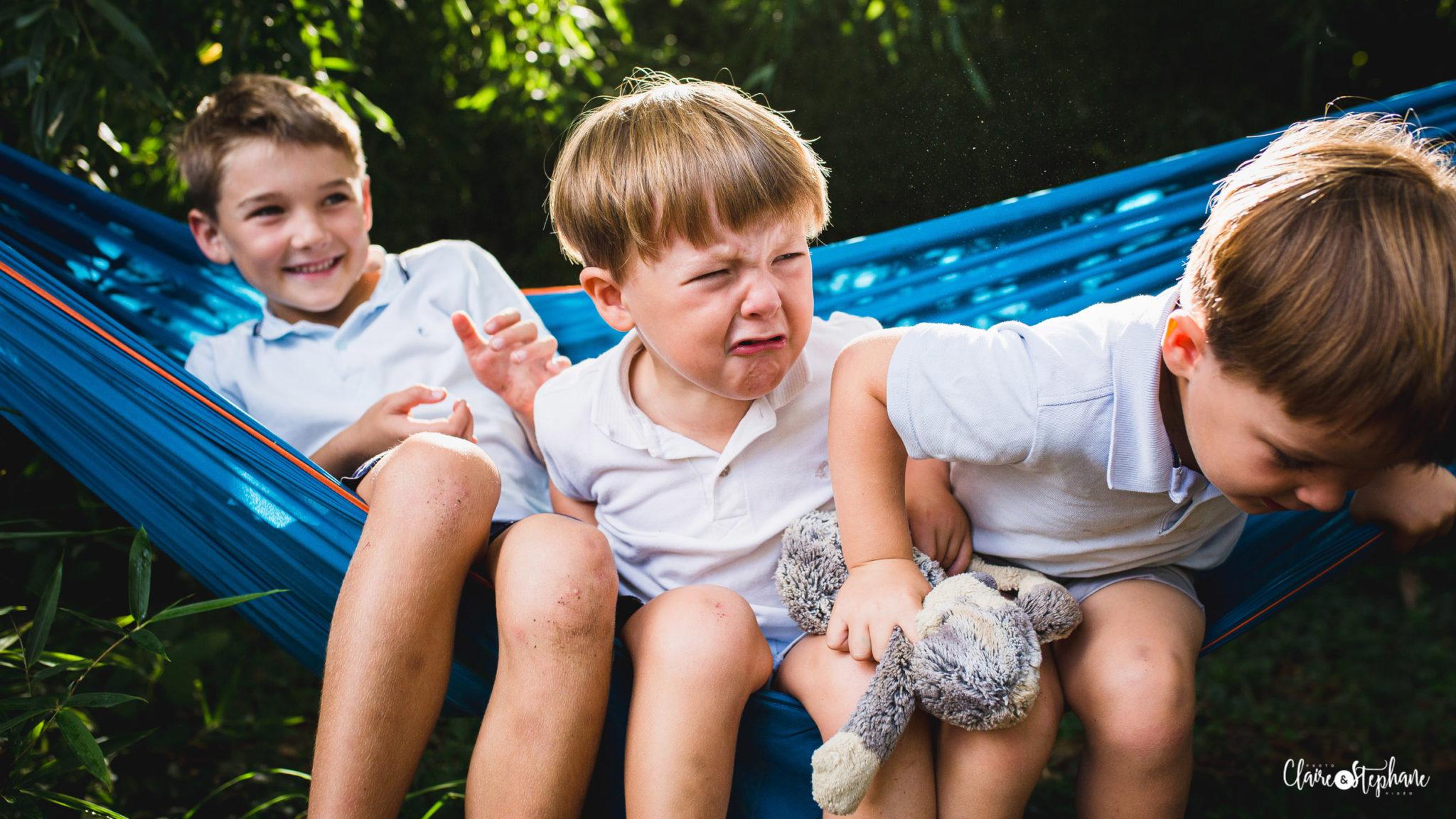 Trois jeunes frères dans un hamac bleus, celui du milieu faire une grimace de pleur