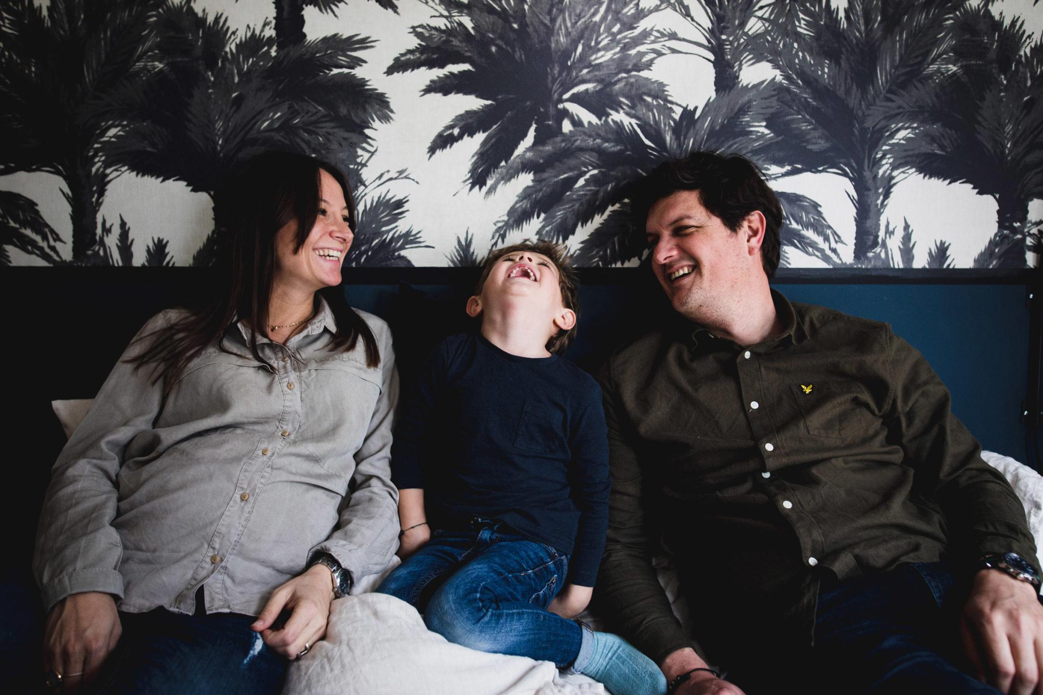 Couple de parent et leur fils qui rient sur un canapé bleu