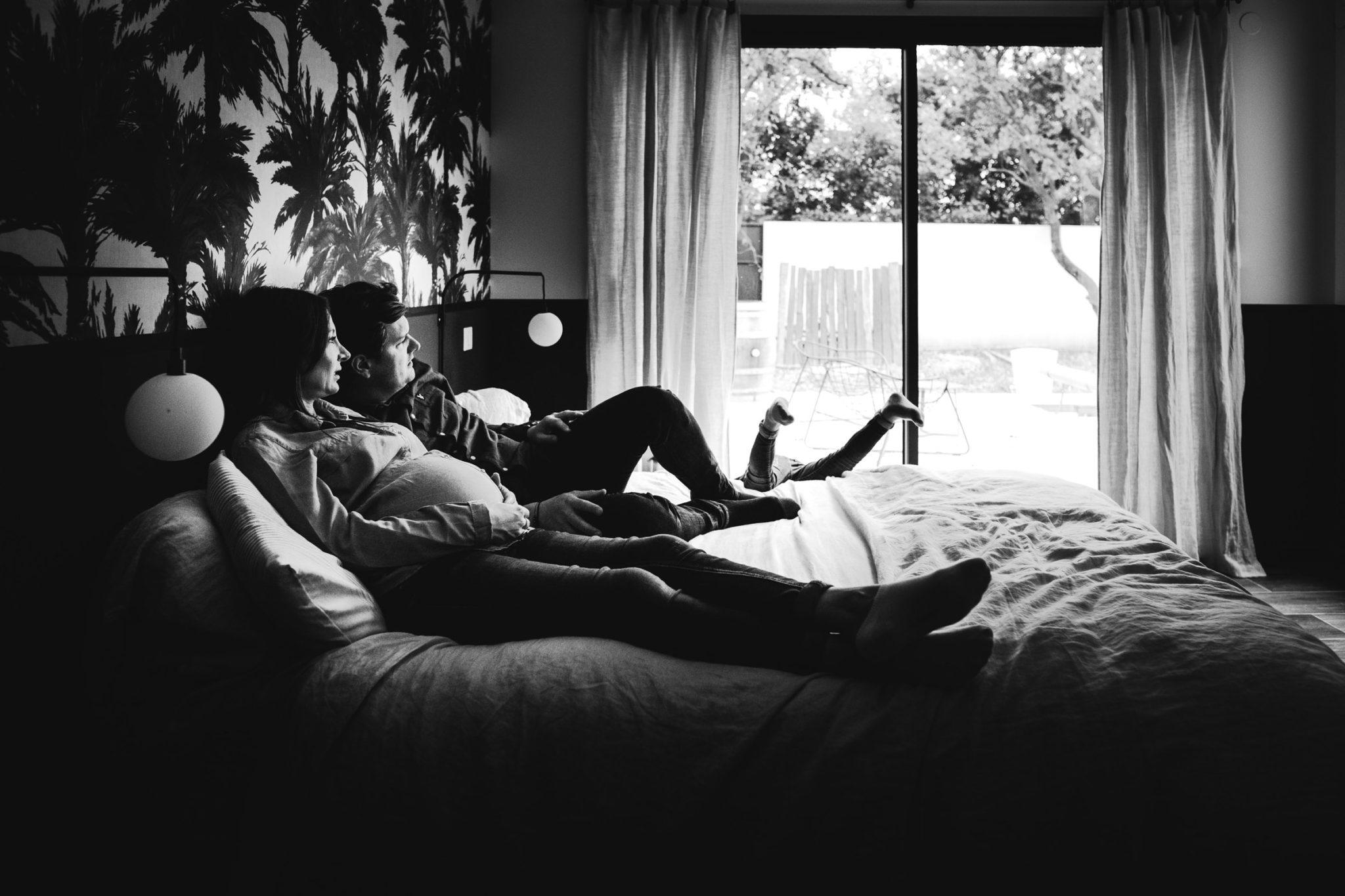 Jeune couple avec la maman enceinte alongé sur le lit, pendant que leur jeune enfant joue